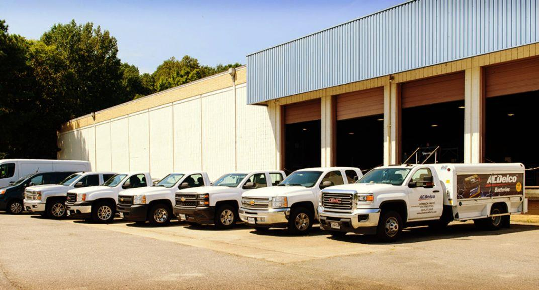 A fleet of delivery trucks in front of the Dominion parts distribution warehouse